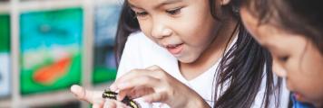 girl holding a caterpillar